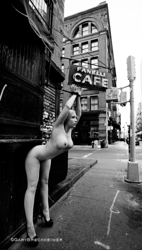 NAked woman tied to a store sign in a shopping street