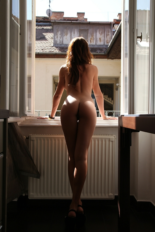Naked girl staring out the window